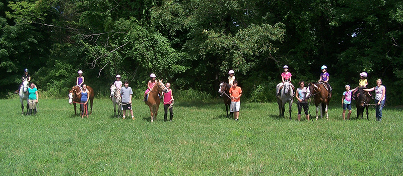 Several People Riding Horses at Camp
